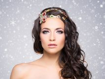 Attractive, curly brunette with flower alike golden headband wit Royalty Free Stock Images