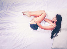 Beautiful brunette lying on bed at home Stock Photography