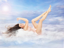 Beautiful brunette lying on clouds Royalty Free Stock Image