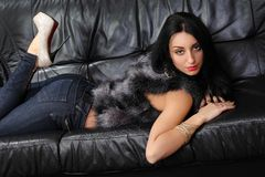 Brunette lying on a leather couch Stock Photo