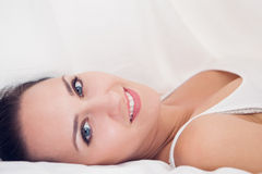 Beautiful brunette lying under the sheets looking at the camera Royalty Free Stock Images