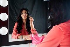 Beautiful brunette makes makeup near mirror Royalty Free Stock Photos