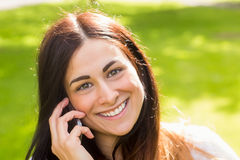 Beautiful brunette making a call in the park Royalty Free Stock Photography
