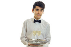 Beautiful brunette male waiter with champagne on tray Royalty Free Stock Images