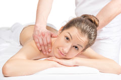 Beautiful brunette on a massage table and masseuse hands. On her back Royalty Free Stock Images