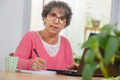 Beautiful brunette mature woman dressed in pink with laptop at home royalty free stock photography