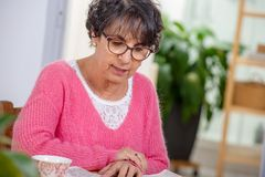 Beautiful brunette mature woman dressing in pink reading newspaper stock photography