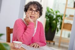 Beautiful brunette mature woman dressing in pink reading newspaper stock images
