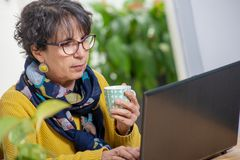 Beautiful brunette mature woman wearing in yellow drinking cup of tea stock photography