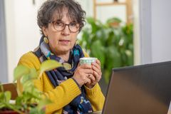 Beautiful brunette mature woman wearing in yellow drinking cup of tea royalty free stock photo