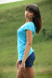 Beautiful brunette on a meadow. Beautiful brunette in a turquoise shirt and denim shorts posing in a nature, on a meadow, fashion photography Royalty Free Stock Images