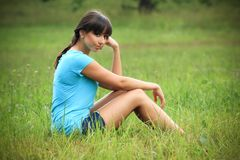 Beautiful brunette on a meadow. Beautiful brunette in a turquoise shirt and denim shorts is sitting in the grass, in a nature, on a meadow, fashion photography Royalty Free Stock Images