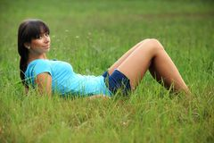 Beautiful brunette on a meadow. Beautiful brunette in a turquoise shirt and denim shorts is sitting in the grass, in a nature, on a meadow, fashion photography Stock Images