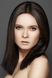 Beautiful brunette with middle hair style, daily eye make-up. Beautiful woman model with perfect dark hair style, natural eye make-up and pale lips, clean skin royalty free stock photo