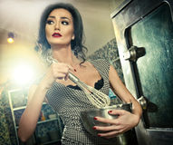 Beautiful brunette mixing ingredients in a bowl. Sensual slim young woman with black bra and low cut neck baking Royalty Free Stock Photo