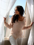 Beautiful brunette model. At a beach house window Royalty Free Stock Photo