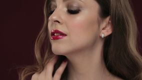Beautiful brunette model with curls, classic makeup and red lips. Beautiful blond model with curls, classic make up and red lips. The beauty of the face stock video