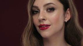 Beautiful brunette model with curls, classic makeup and red lips. Beautiful blond model with curls, classic make up and red lips. The beauty of the face stock footage