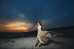 Beautiful Brunette Model Girl With Long Sexy Legs In Fashionable Lace Dress Posing At The Sea Coast At The Sunset With Royalty Free Stock Photos