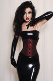 Beautiful brunette model wearing black latex Royalty Free Stock Photos