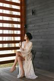 Beautiful brunette model woman with perfect body in the fashionable lingerie on the dark wooden verandah royalty free stock photography