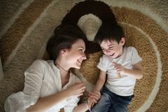 Beautiful brunette mom kisses and hugs with son home. Beautiful brunette mom kisses and hugs with her son on the floor in a home-like normal real interior, brown Stock Photography
