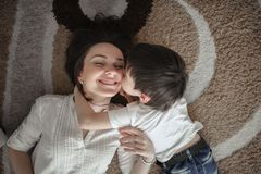 Beautiful brunette mom kisses and hugs with son home. Beautiful brunette mom kisses and hugs with her son on the floor in a home-like normal real interior, brown royalty free stock photos