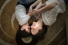 Beautiful brunette mom kisses and hugs with son home. Beautiful brunette mom kisses and hugs with her son on the floor in a home-like normal real interior, brown royalty free stock image