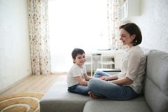 Beautiful brunette mom and son hugging on couch. Beautiful brunette mom and son hugging on the couch in a real interior, soft focus and light tone royalty free stock images
