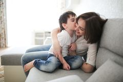 Beautiful brunette mom and son hugging sofa. Beautiful brunette mom and son hugging on sofa in real interior, soft focus royalty free stock images