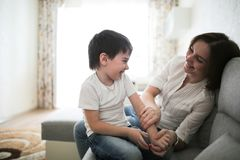 Beautiful brunette mom and son hugging sofa. Beautiful brunette mom and son hugging on sofa in real interior, soft focus stock image