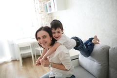 Beautiful brunette mom and son hugging sofa. Beautiful brunette mom and son hugging on sofa in real interior, soft focus royalty free stock photo