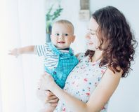 Beautiful brunette mother with baby boy. Smiling for a magazine in the studio royalty free stock image
