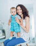Beautiful brunette mother with baby boy. Smiling for a magazine in the studio stock photography