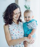 Beautiful brunette mother with baby boy. Smiling for a magazine in the studio stock images