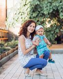 Beautiful brunette mother with baby boy. Smiling for a magazine in the studio stock photo