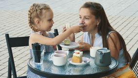 Mother and her cute little daughter in outdoor cafe. Beautiful brunette mother and her cute little daughter sitting in outdoor summer cafe. Happy family drinks stock video footage