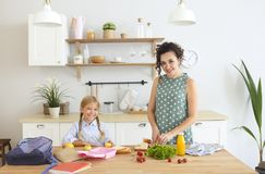 Beautiful brunette mother and her daughter packing healthy lunch and preparing school bag royalty free stock photos