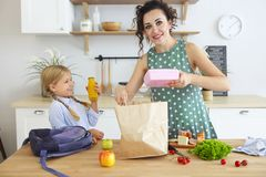 Beautiful brunette mother and her daughter packing healthy lunch and preparing school bag stock photography