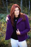 Beautiful brunette in nature. Beautiful brunette in a black shirt, purple coat and white jeans posing in a nature, fashion photography Stock Photo
