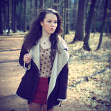 Beautiful brunette in nature. Beautiful brunette in dots shirt and red scarf and coat posing in nature, fashion photography, cross processing, square composition Royalty Free Stock Images