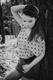 Beautiful brunette in nature. Beautiful brunette in dots shirt and scarf posing in nature, fashion photography, black and white photo, imitation of film grain Royalty Free Stock Photography
