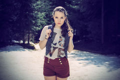 Beautiful brunette in nature. Beautiful brunette in shirt and red shorts and blue vest posing in nature, fashion photography, cross processing Royalty Free Stock Images