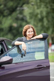 Beautiful brunette near the opened door of new car Royalty Free Stock Photos
