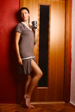 Beautiful brunette in a nightdress. Posing at the door, in a room, fashion and boudoir photography Stock Photos