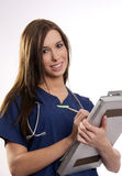 Beautiful Brunette Nurse Records Patient Medical Chart Data on C Stock Photo