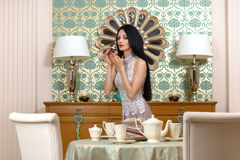 Beautiful brunette  it offers a taste of the cake. Royalty Free Stock Photography