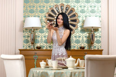 Beautiful brunette  it offers a taste of the cake. Royalty Free Stock Image