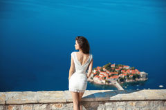 Beautiful brunette over blue sky posing in white dress. holidays Royalty Free Stock Image