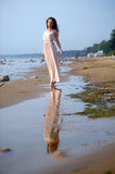 Beautiful brunette in pale pink long dress. On the beach royalty free stock photo